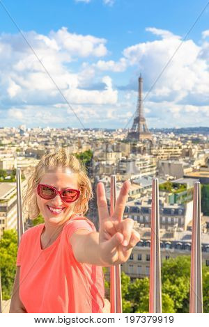 Traveler freedom Europe concept. Caucasian lifestyle traveler woman at top of Arc de Triomphe. Tour Eiffel and Paris skyline on blurred background. Landmark in Paris, France, Europe.Sunny day blue sky