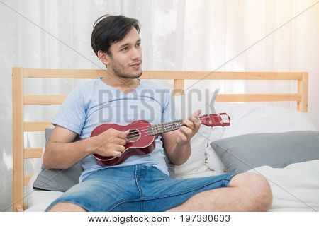 Young man play ukulele song on bedroom.