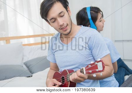 Couple Relaxing With Happiness And Joyful And Play Ukulele Song In Bedroom
