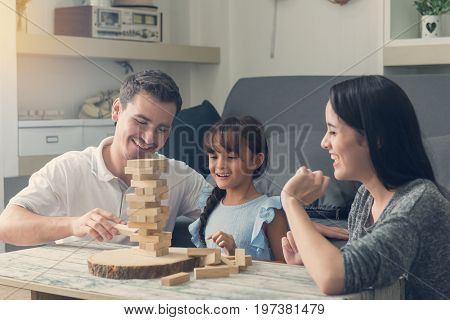 Happy Family And Daughter Playing The Wooden Blocks Tower At Home