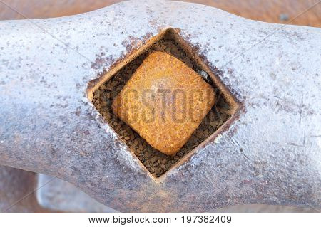 Rusting bolt set in horn cleat on dock