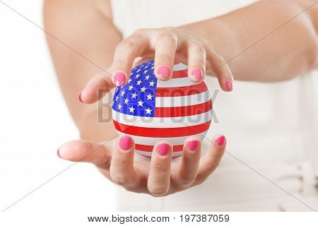 Two Woman Hands Protecting USA Flag Earth Globe Sphere on a white background.