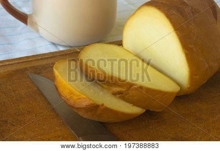 cut head of traditional Adygei cheese handmade with knife and a Cup of coffee on wooden Board
