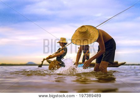 Children Fisherman boy and girl with catching fish and fisherman throwing nets on boat on lake river thailand