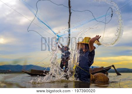Children Fisherman Girl with catching fish splash water and fisherman throwing nets on boat on lake river thailand