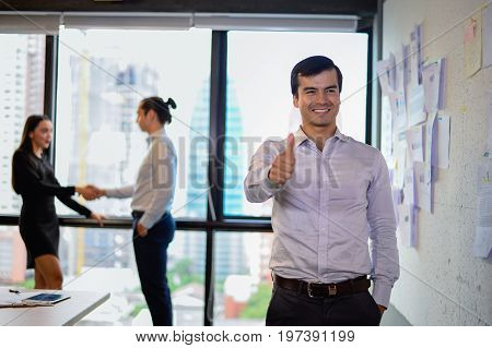 handsome business man smile and stand and show thumb up at the office successful concept