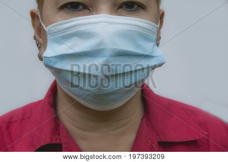 Woman suffer from sick and wearing face mask. Woman in protective mask feeling bad.