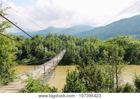 Suspended wooden bridge across Schodnica river in Carpathians Ukraine