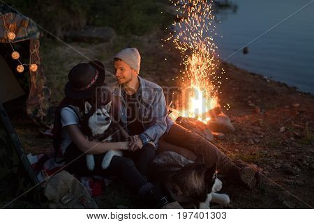 Couple looking at each other with dogs in tent on nature sitting with two Husky near fire on nature.