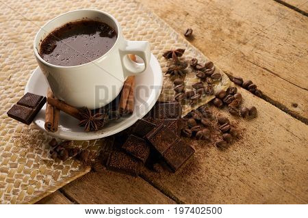 Cup with hot coffee and arabica coffee beans with broken dark chocolate cocoa powder cinnamon sticks and anise on wooden rustic table.