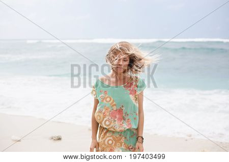 Horizontal portrait of blonde girl in colorful dress with hair floating in the air is standing near the ocean and looking down
