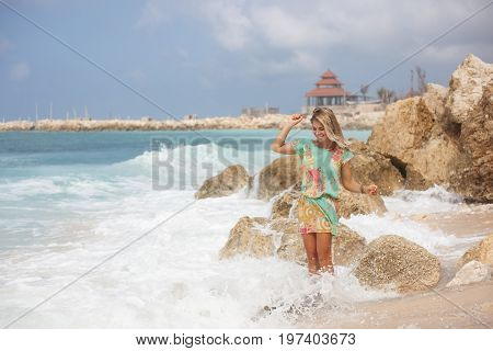 Horizontal portrait of beautiful happy blonde girl in colorful dress is standing on the beach in front of stones and looking down with hands in the air