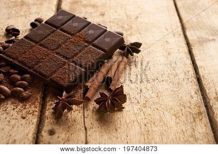 Cinnamon sticks dark chocolate bar arabica coffee beans anise and cocoa powder on wooden old rustic background