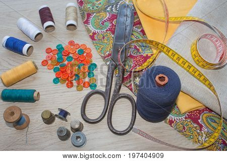 scissors and sewing kit includes threads of different colors thimble and other sewing accessories on wooden table. tools for sewing for hobby