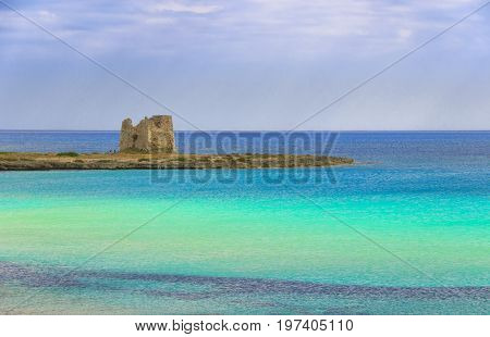 Sea colors of Italy. Apulia coast : Marina di Lizzano beach,Torre Sgarrata watchtower.The coastline is characterized by a alternation of sandy coves and jagged cliffs overlooking a truly clear and crystalline sea.