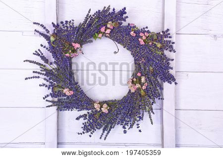 Lavender wreath hanging on wood wall in barn