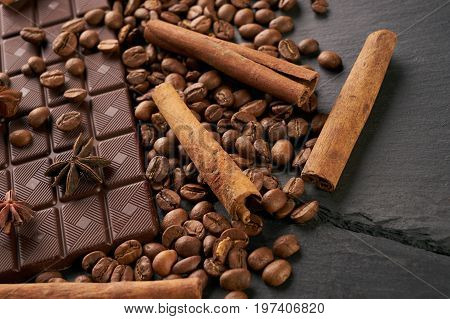 Coffee beans and cinnamon on a black stone background. Roasted arabica coffee beans pile with cinnamon stick and anise spice ingredients for fragrant coffee.