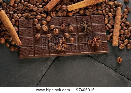 Top view of arabica coffee beans cinnamon star anise dark chocolate on black stone background with copy space