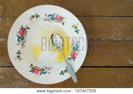 Empty plate with the remnants of honey with a teaspoon is on a wooden old table