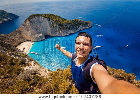A guy doing selfie on a background of a shipwreck