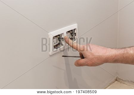 The hands of an electrician installing a wall power socket