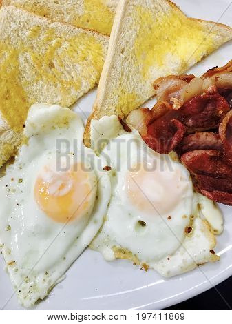 Cooked breakfast with fried eggs, crispy bacon and white toast