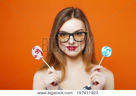 Funny Young Girl Covers Her Eyes With Two Lollipops On Orange Background. Attractive Brunette With R