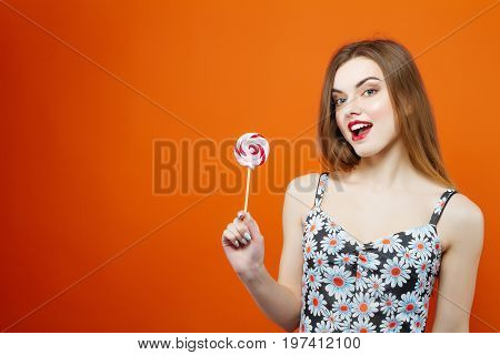 Female Hands Holding Colorful Lollipops On Orange Background In Studio.