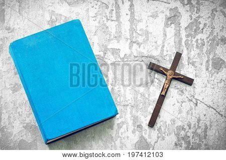 Closeup of wooden christian cross and bible on the white background. Church utensils.