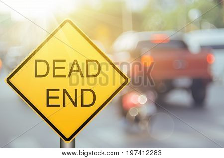 Dead End Warning Sign On Blur Traffic Road With Colorful Bokeh Light Abstract Background.