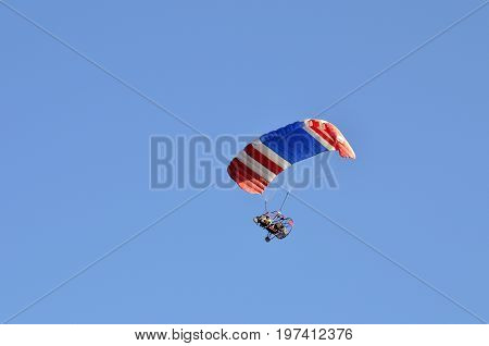 Flight of a motor-paraplan with a white-red-blue striped wing against a blue sky