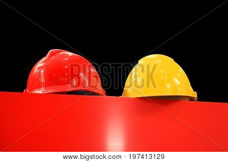 Red and yellow hard hats on a red table on black background
