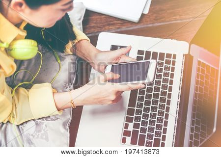Happy Woman Using Smart Phone And Laptop Computer. Vintage Effect Tone.