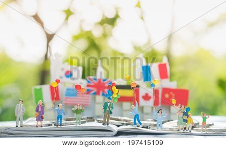 Tiny miniature model of multi-generation family holding a balloons with international flags background using as Relationship Family Generations Togetherness Concept.