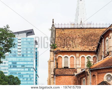 Architecture in Ho Chi Minh City with the old Saigon Notre-Dame Basilica in the foreground to the right and the modern Vincom Center in the background to the left in the background.