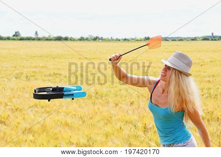 The Blonde Girl In White Hat With A Fly Swatter Drives Away Drone, Against Wheat Field