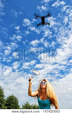 The Blonde Girl In Sunglasses With A Fly Swatter Drives Away Drone, Against Blue Sky With White Clou