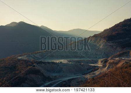 Quarry (open pit) for mining gravel at sunset in the mountains. Mining industry concept