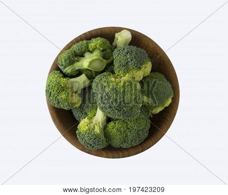 Broccoli in wooden bowl. Top view. Broccoli isolated on a white background. Broccoli with copy space for text.