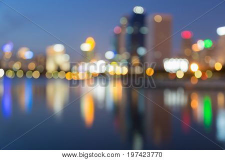 Twilight blurred bokeh and reflection city office building abstract background