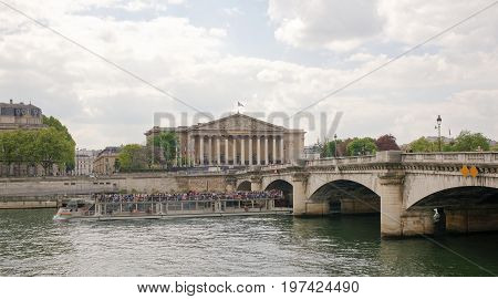 ParisFrance- April 29 2017: View of the National Assembly. Under the bridge floats ship with tourists on board