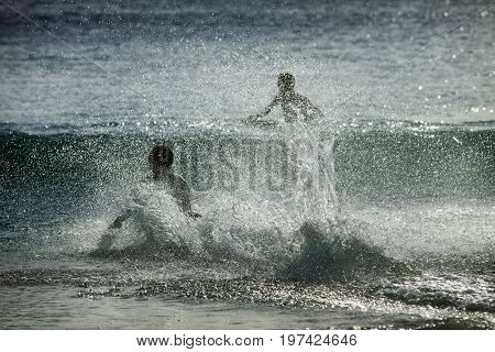Silhouettes of people in the splashes of the ocean at sunset