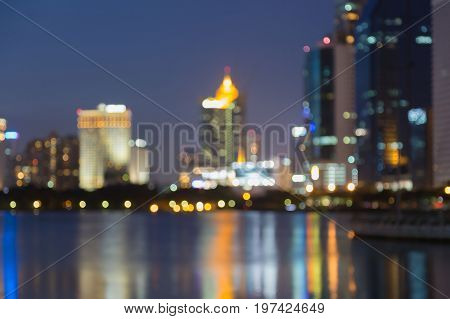 Blurred bokeh light city office building with water reflection abstract background