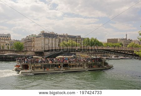 ParisFrance- April 29 2017: Under the bridge Leopold Sedar Senghor floats boat with tourists