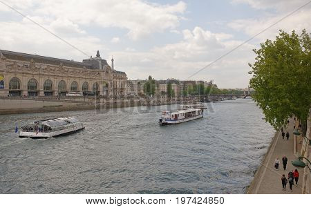ParisFrance- April 29 2017: On the river Seine sailing ships with tourists. Pedestrians walk and rest