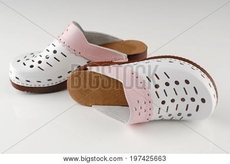 Pair of modern clogs on gray background
