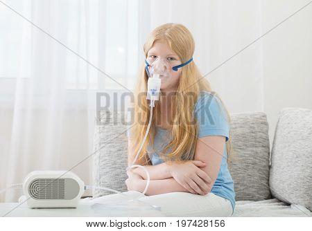 the teenager girl doing inhalation on sofa