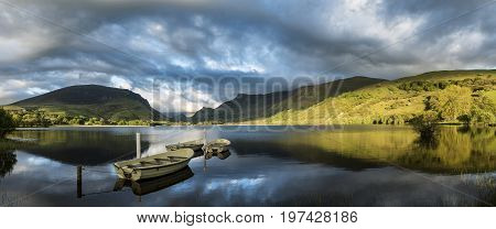 Stunning Panorama Lake Landscape With Rowing Boats In Foreground And Mountain Range In Background