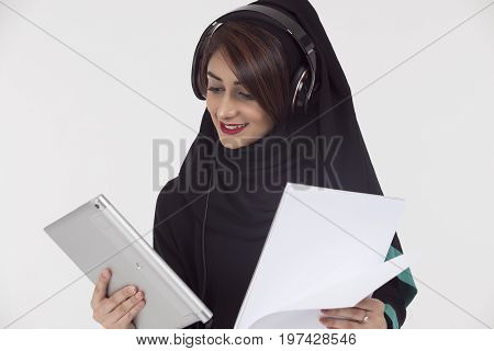Arabic student wearing abaya holding White paper and tablet