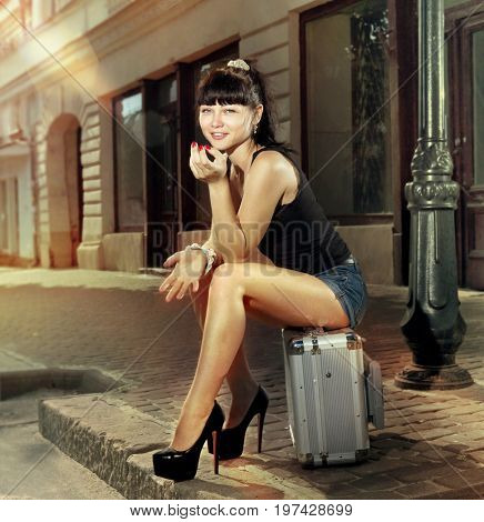 woman sits on suitcase near road in small city